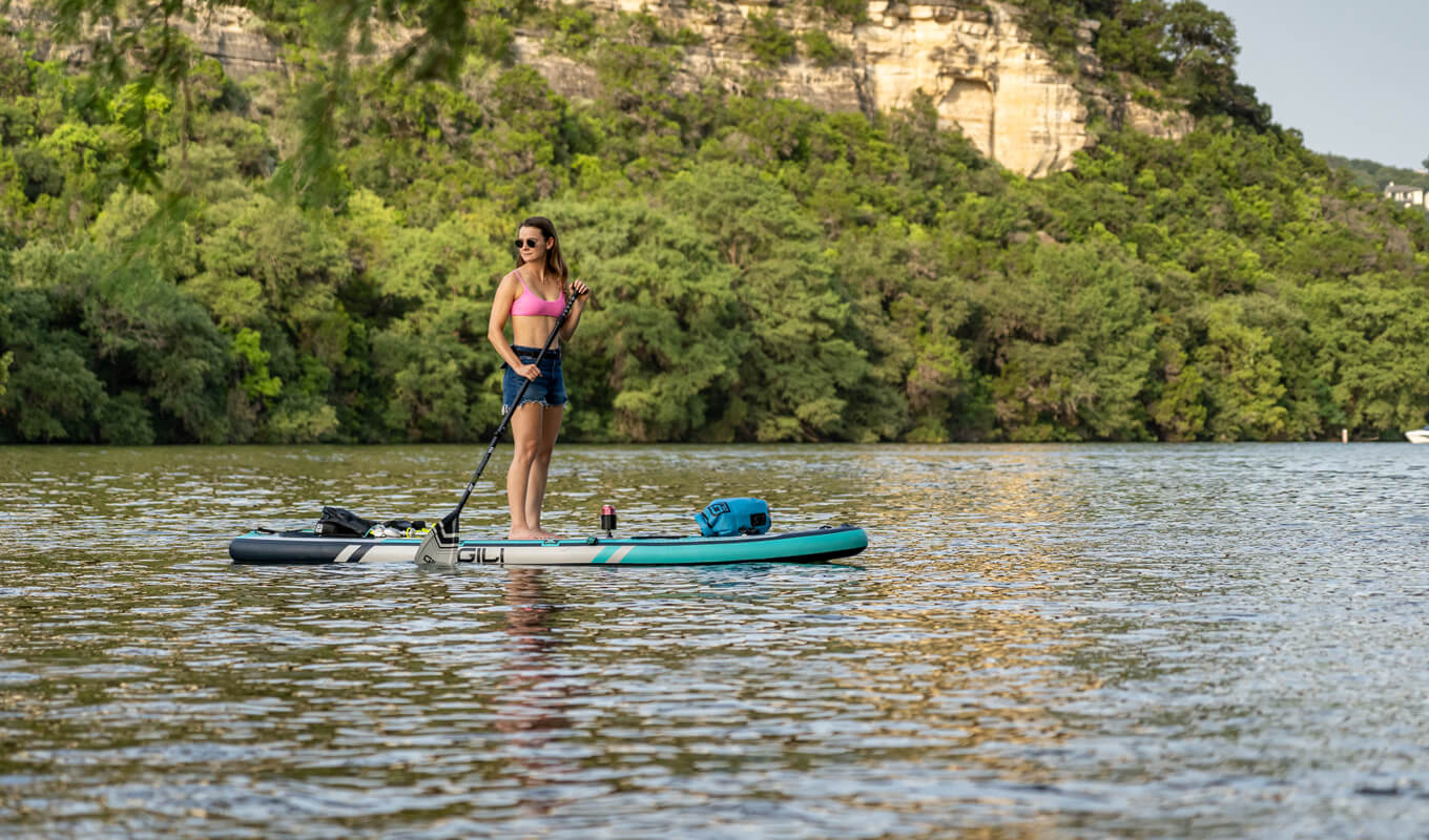 Woman paddle boarding on a pink top