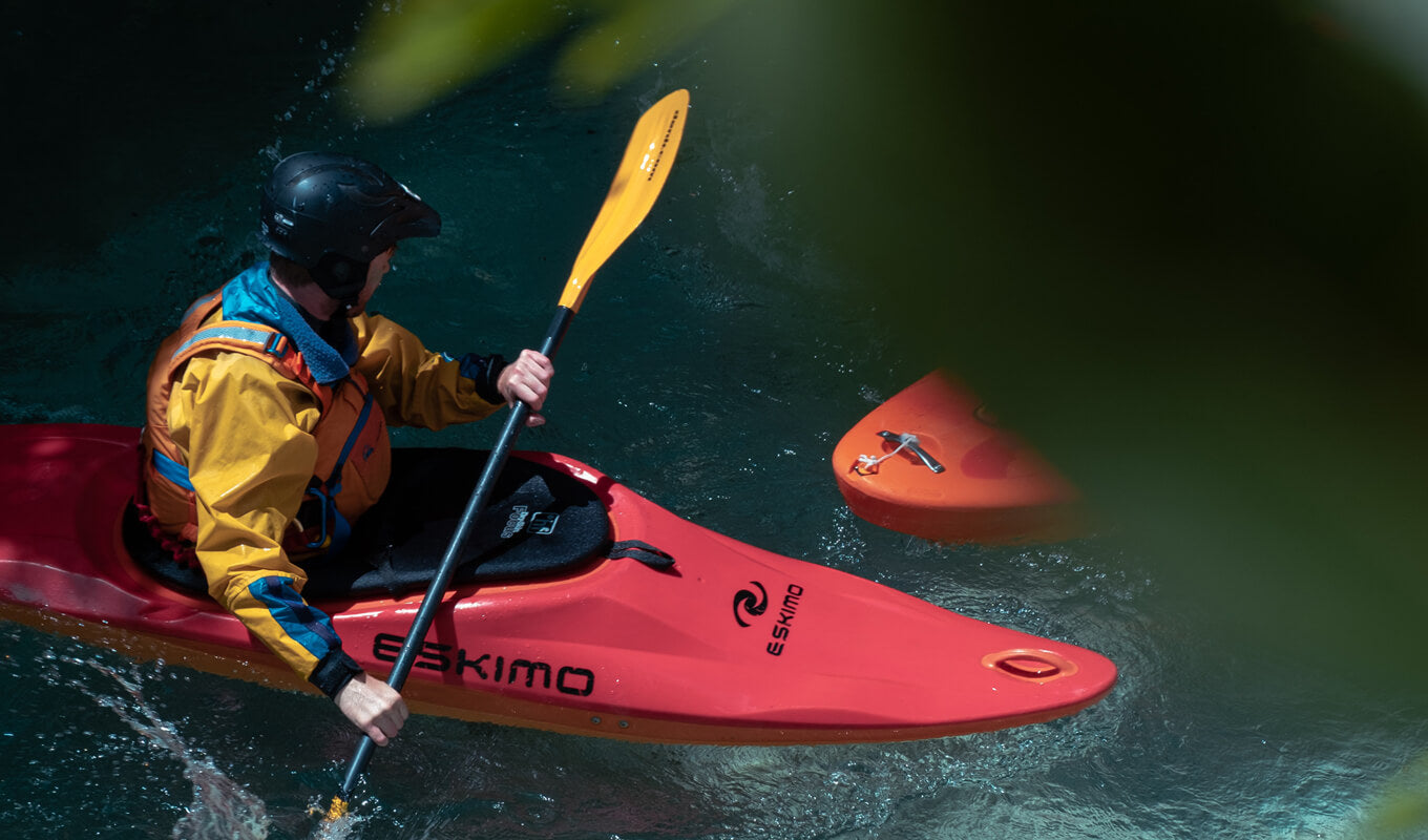 Man wearing of yellow and red life vest on a whitewater kayak