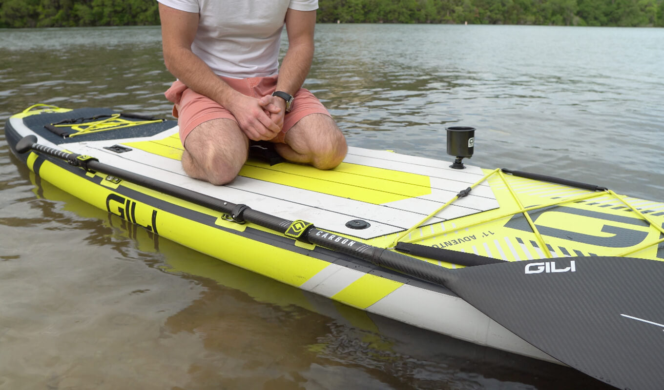 Man on a yellow SUP board with paddle holder