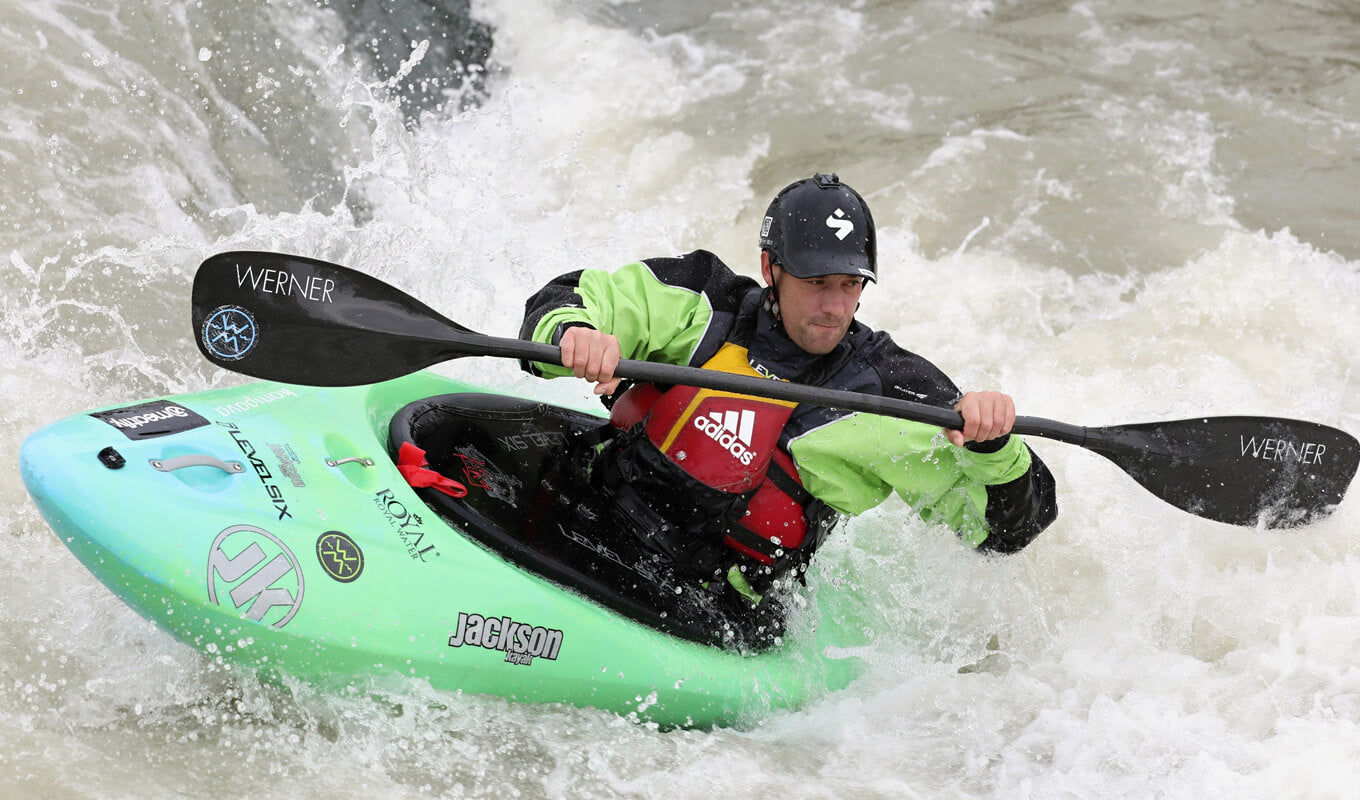 Man compete on a green whitewater kayak