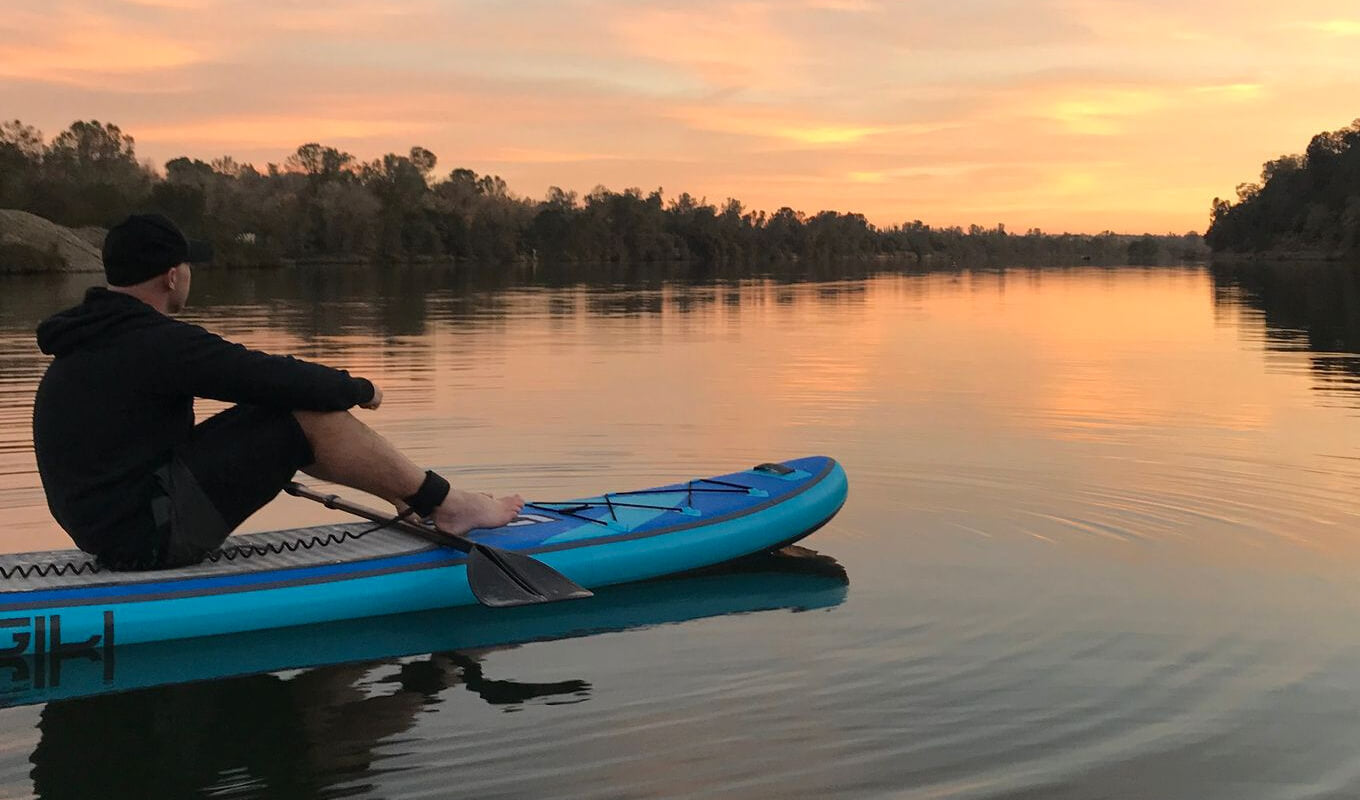 Man on an SUP wearing SUP ankle leash while watching sunset