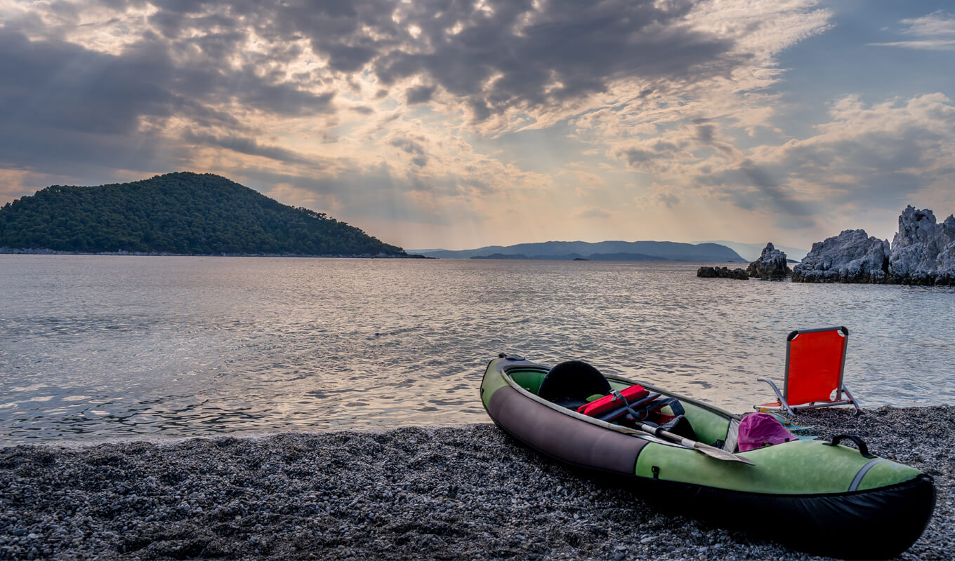 green inflatable kayak on shore