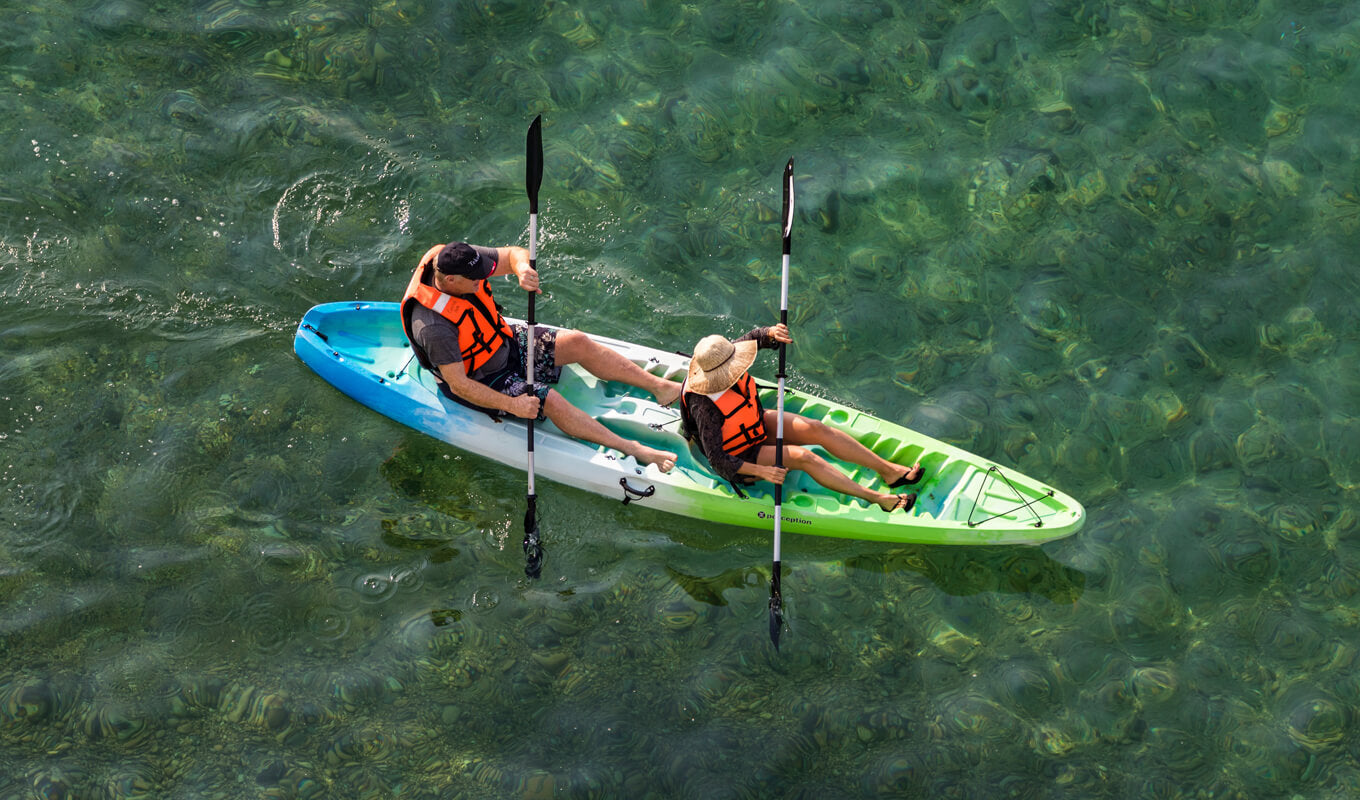 Man and a woman wearing an orange life jacket on a sit on top kayak