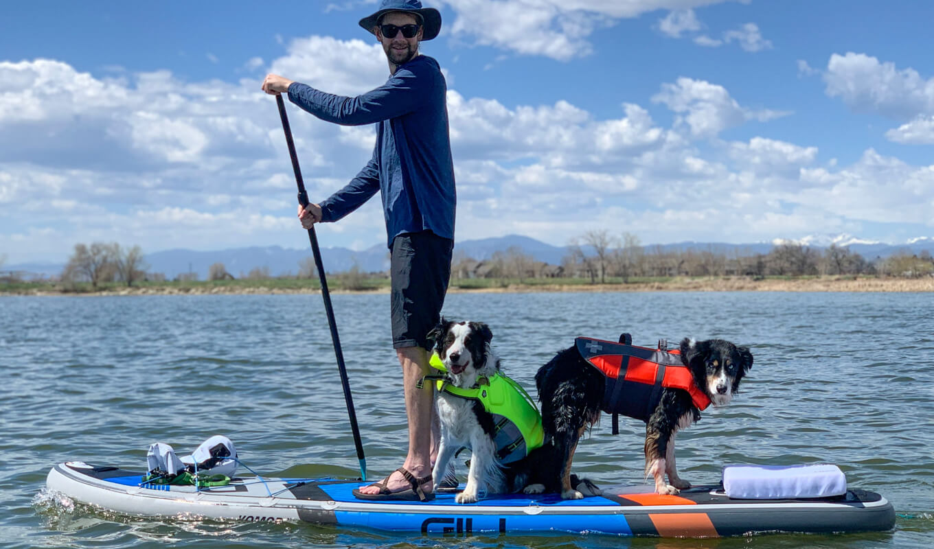 Man with his two dogs on a life jacket