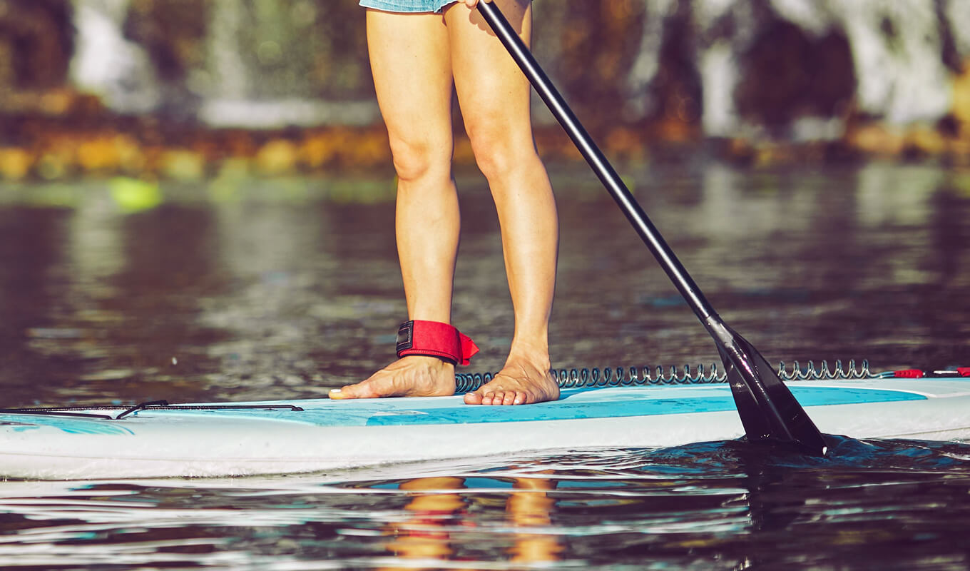 Women wearing red SUP leash on her paddle board