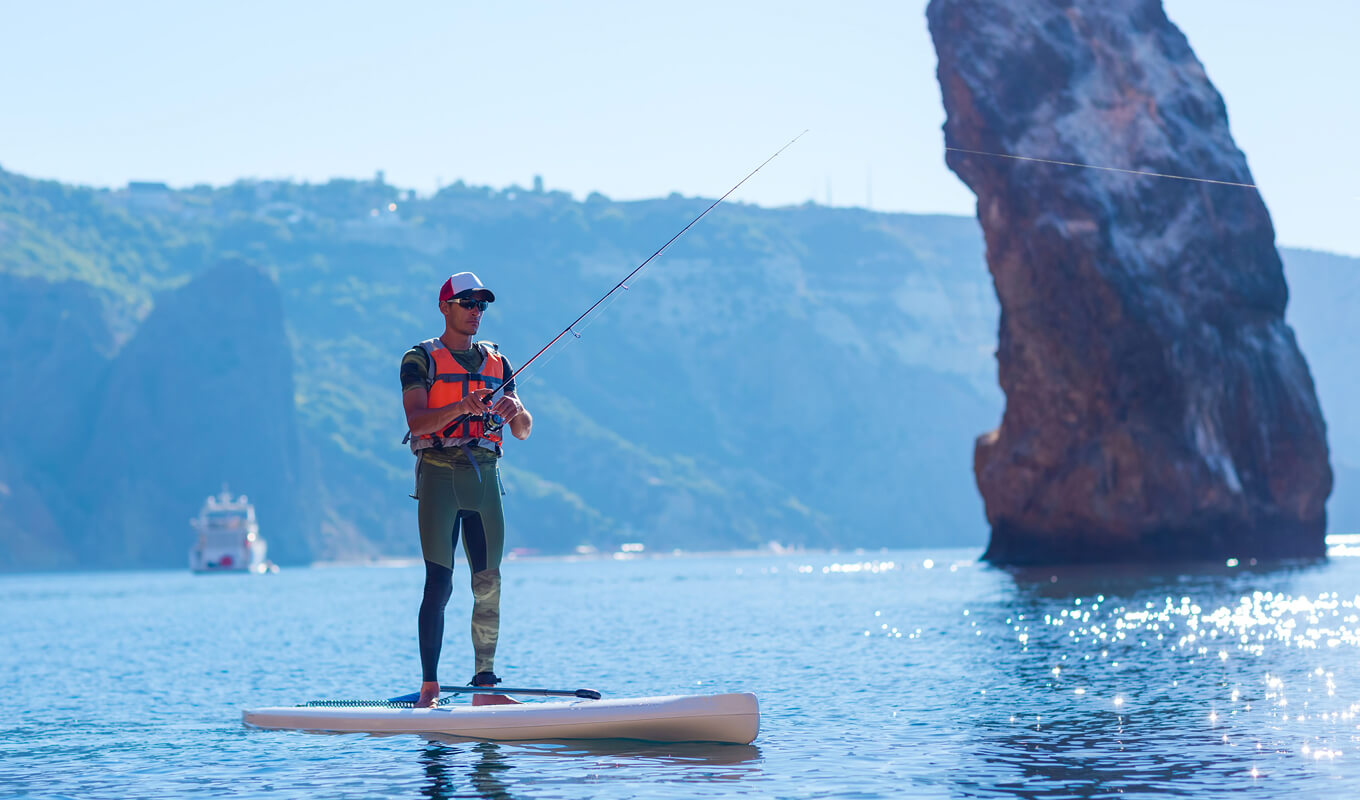 Man fishing using inflatable paddle boards