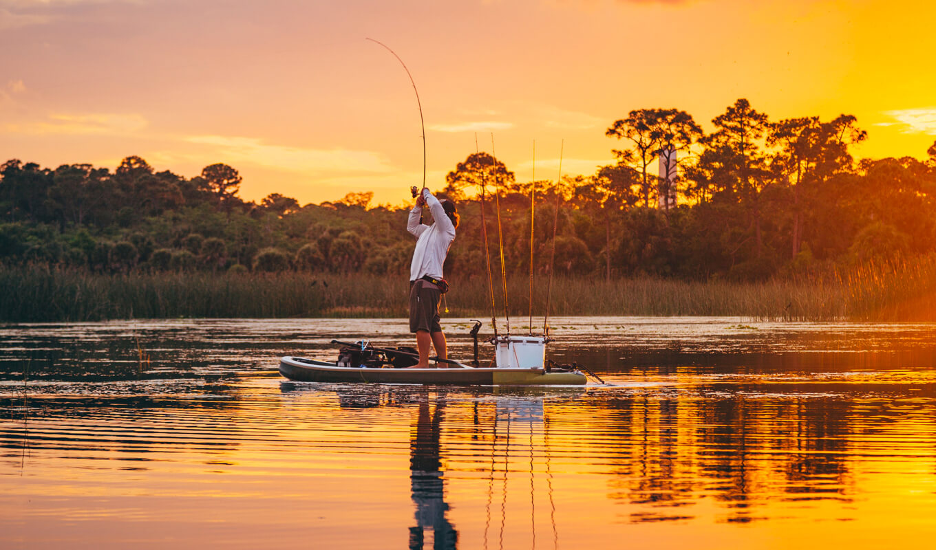 Man fishing on a lake using SUP with complete setup