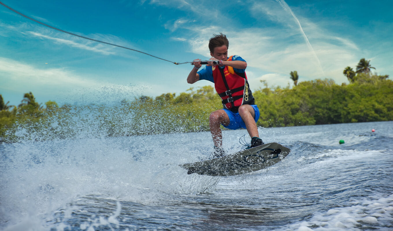 Man wakeboarding using a red life jacket
