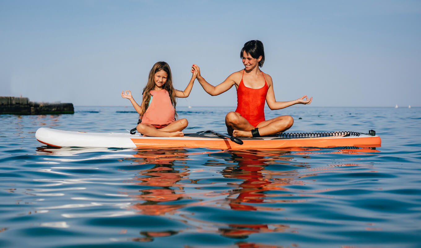 Mom and daughter doing yoga on a paddle board