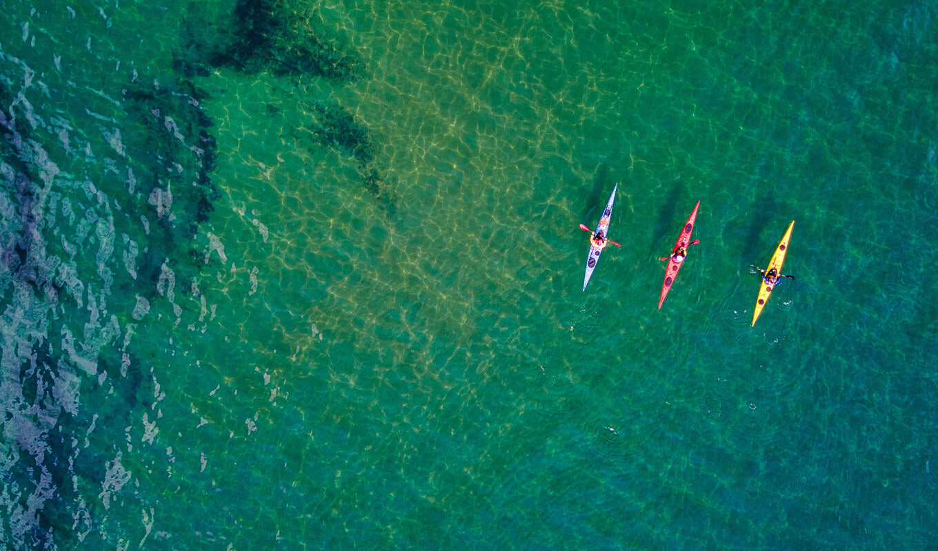 Red, yellow and blue kayak in the ocean