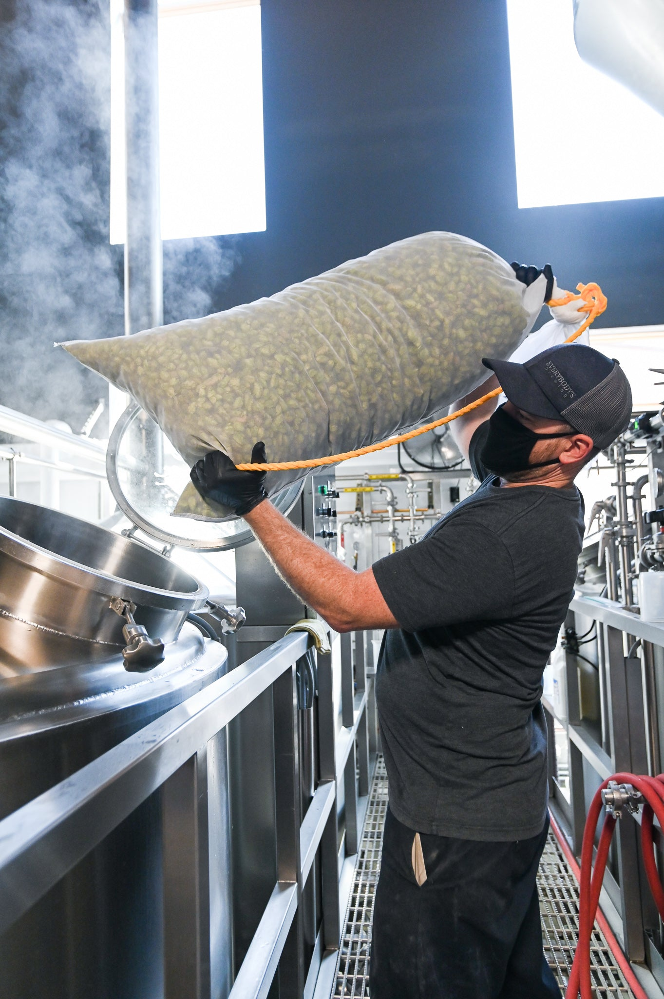 Head Brewer Dave McGinley loads hops into tank for Head Stash Fresh Hop IPA