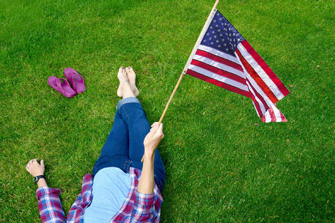 NuuSol-Girl laying in grass with a pair of Rustic Wine flip flops lying next to her. She's holding an American flag.