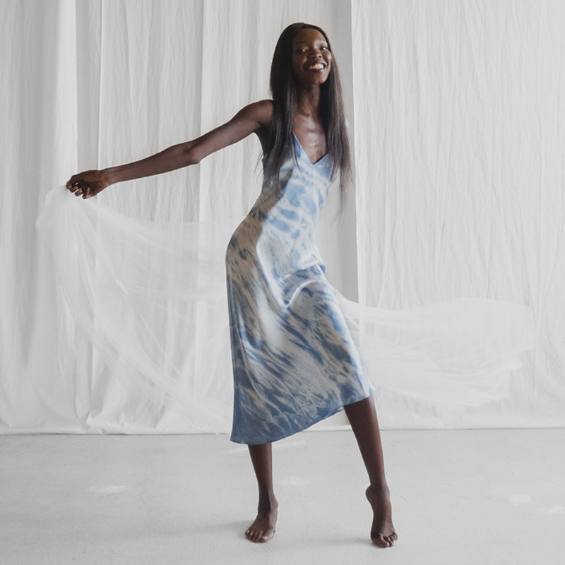 Model wearing the 'Making Waves' Silk Slip Dress holding fabric