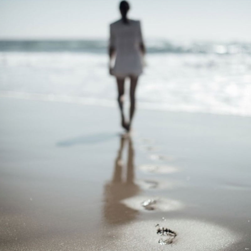 woman walking towards sea with footprints in sand