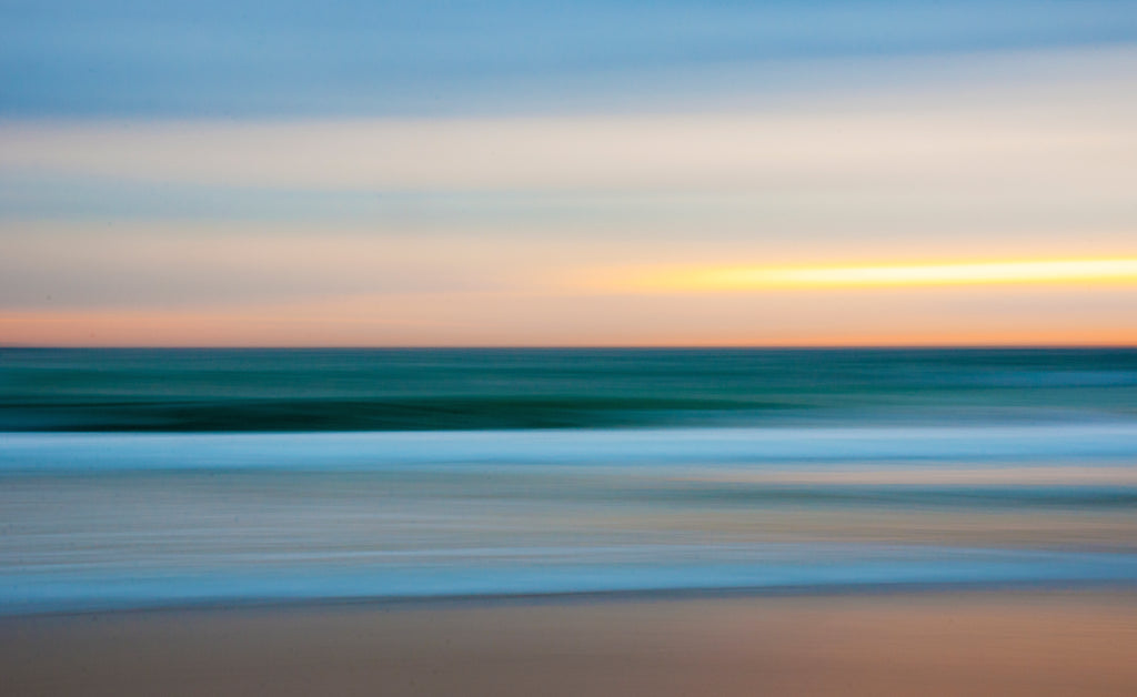 slow shutter with lens on continuous focus whilst panning slightly to the right at sunrise in manly the sea and that