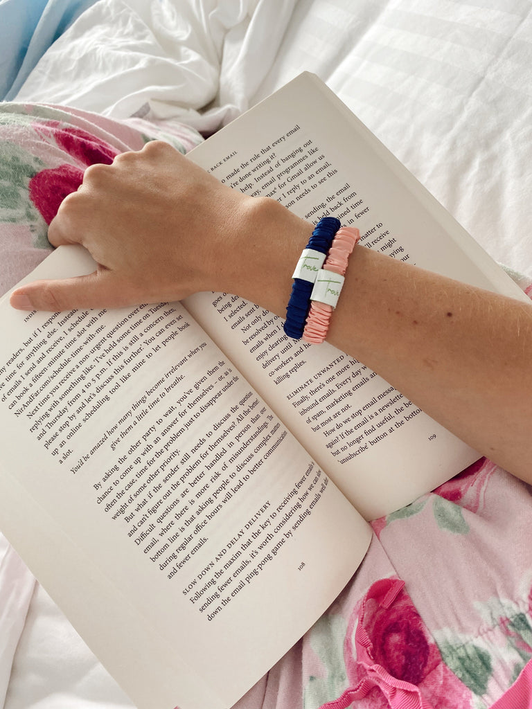 Lifestyle photo of girl wearing two scrunchies on her wrist, one is navy blue and one is baby pink.