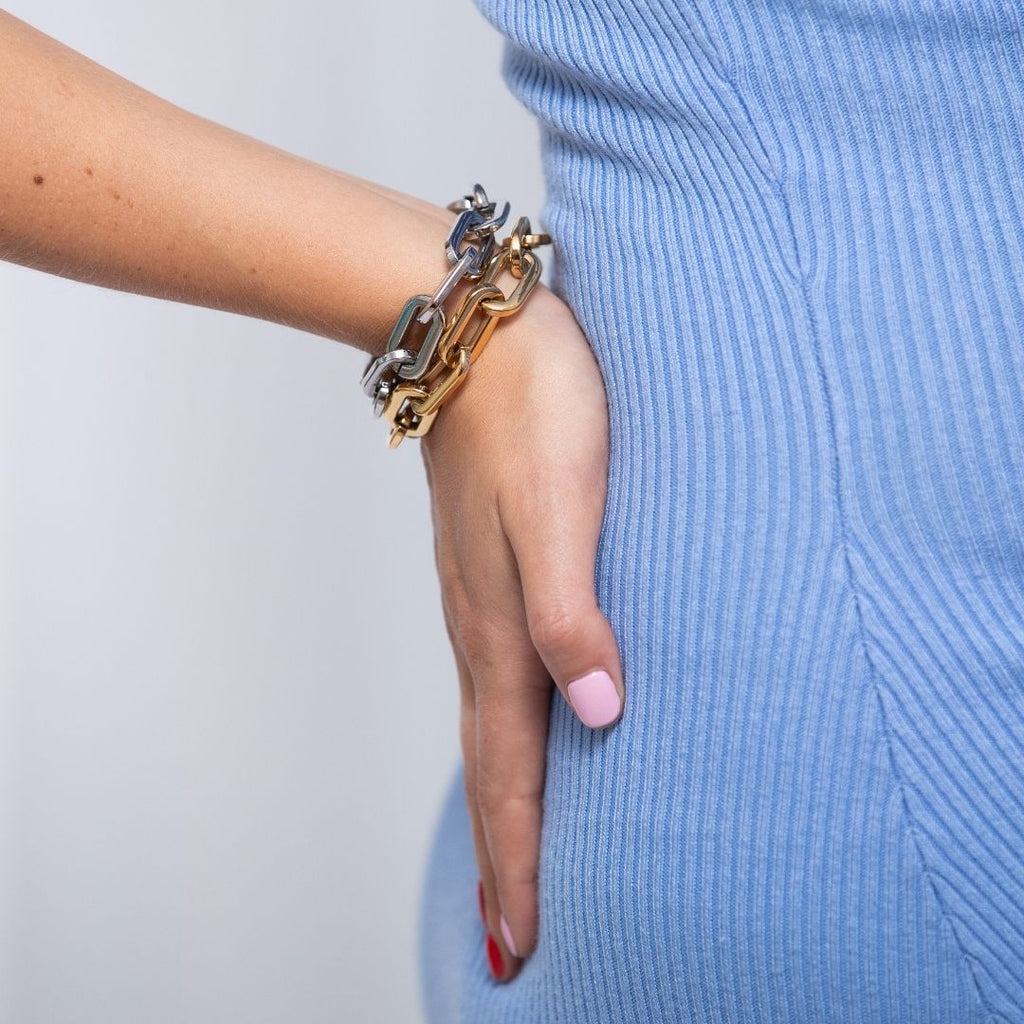 Girl wearing a pair of chunky chain bracelet in gunmetal silver and gold.