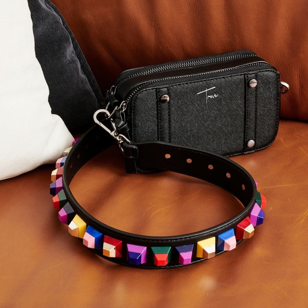 Black vegan leather handbag strap with coloured acrylic embellishments attached to small, black camera style handbag sitting on brown leather couch.