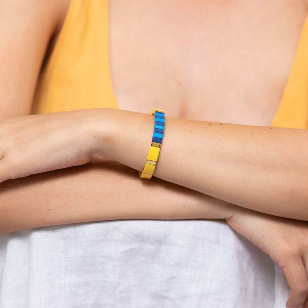 Girl wearing colourful elasticised bracelet with square metal beads coated in a mix of yellow, sky blue and navy blue enamel.