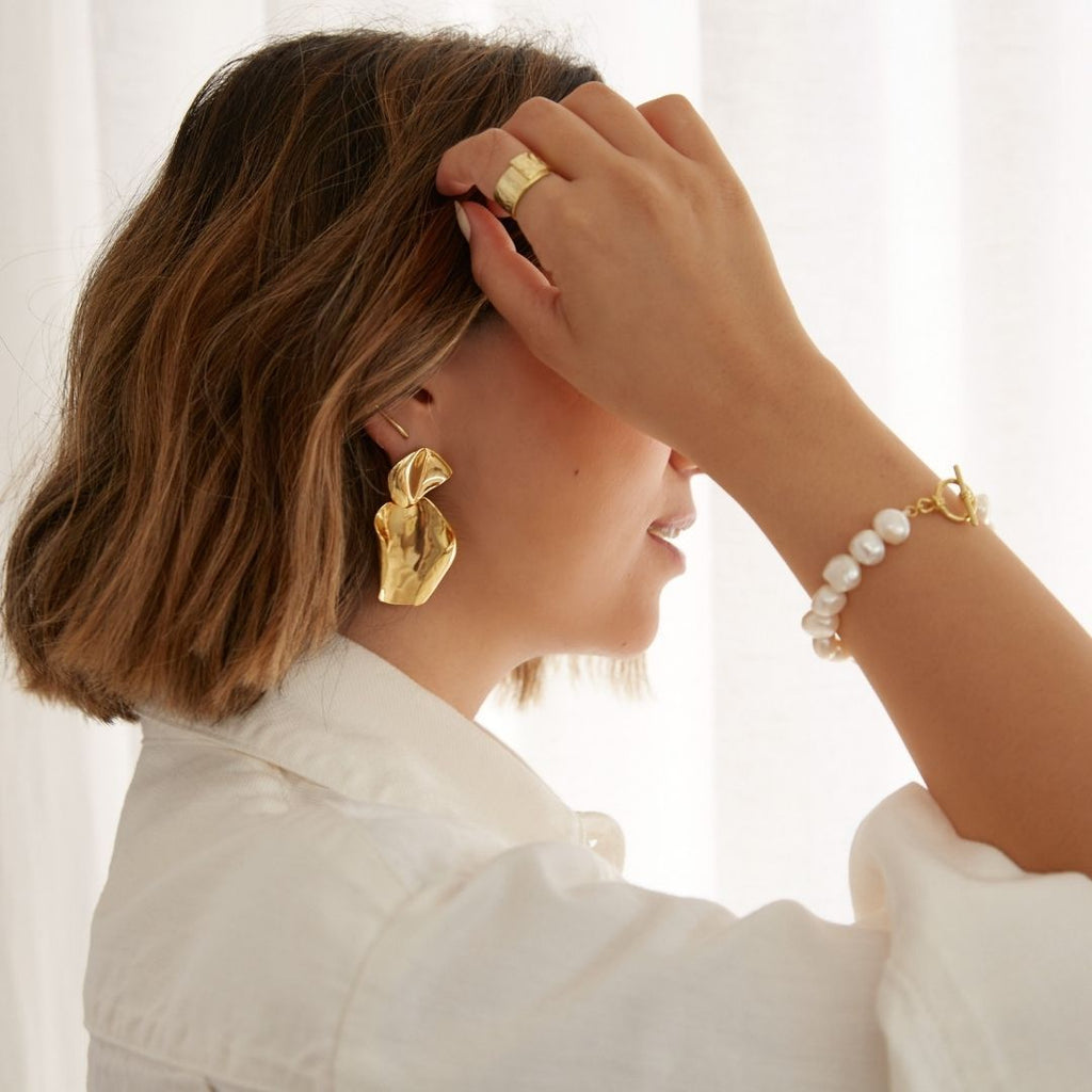 Girl with brunette bob wearing freshwater pearl bracelet, thick gold ring and statement gold earrings.