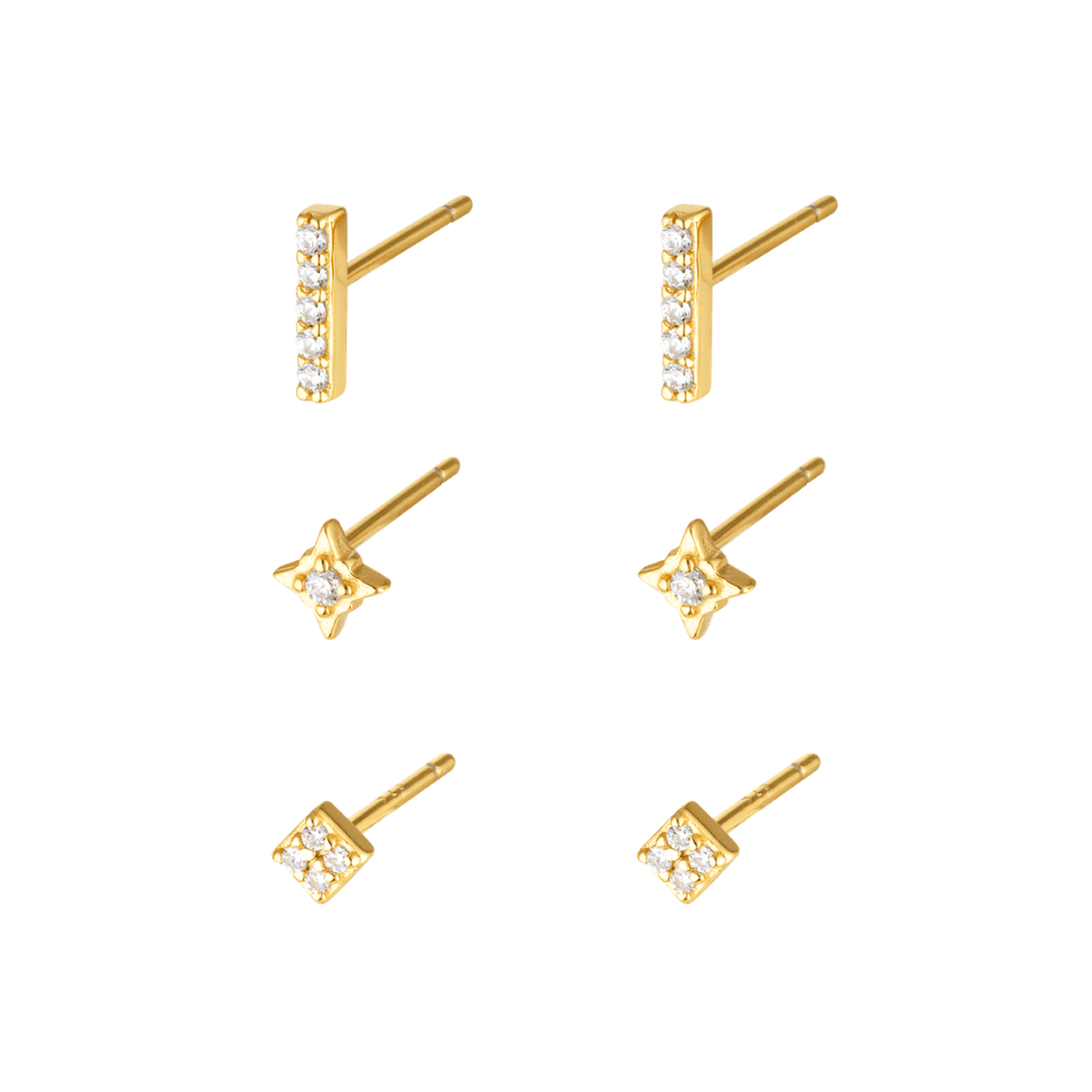 Stock image of gold studs, sold in a three pack, in gold embellished with clear mineral zircon stones. The first earring is a line shape, the second a star shape and the third a square shape.