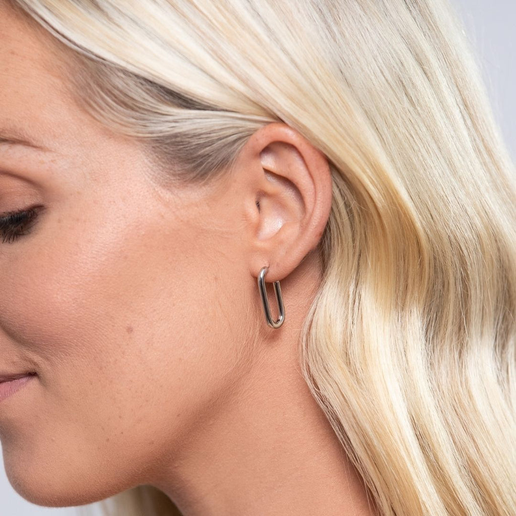 Girl wearing stainless steel, chain drop earrings with one loop. Up to three loops can be added to the earring.