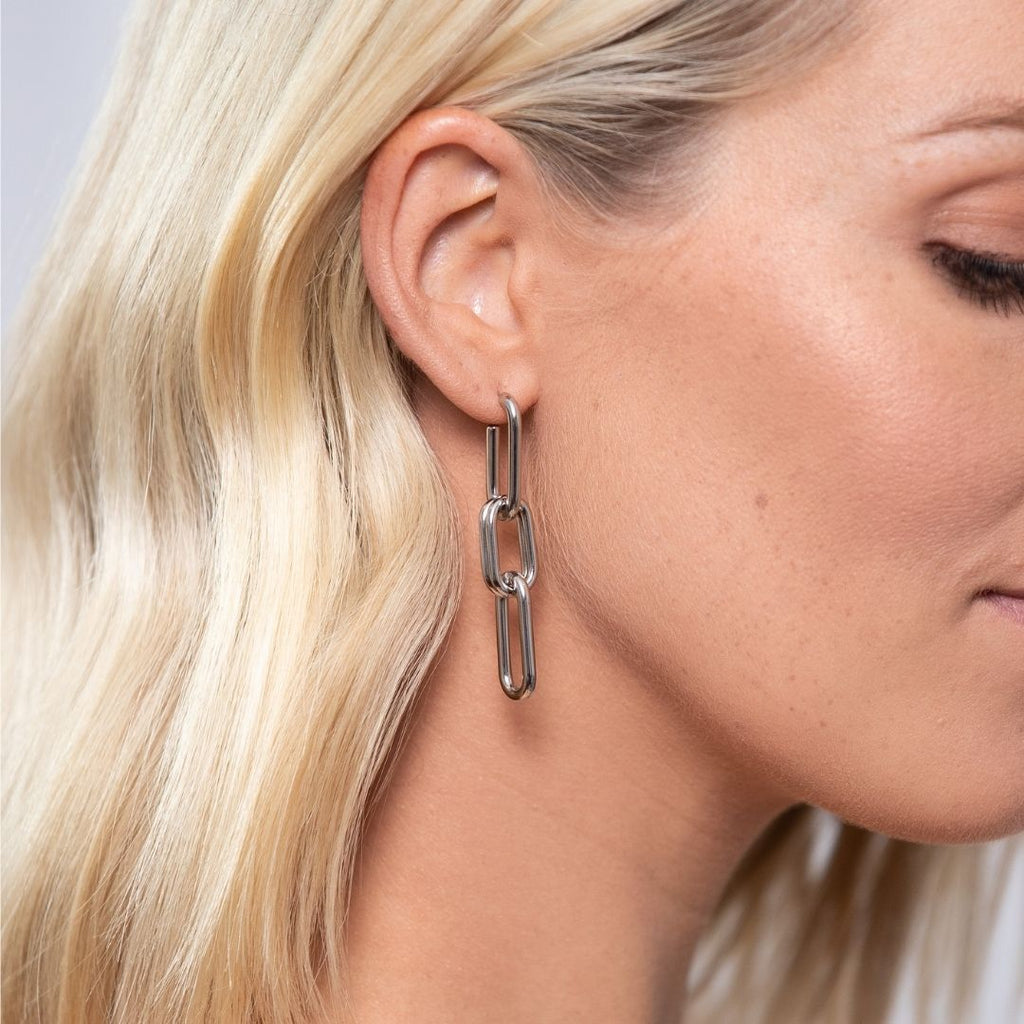 Girl wearing stainless steel, chain drop earrings with four loops.