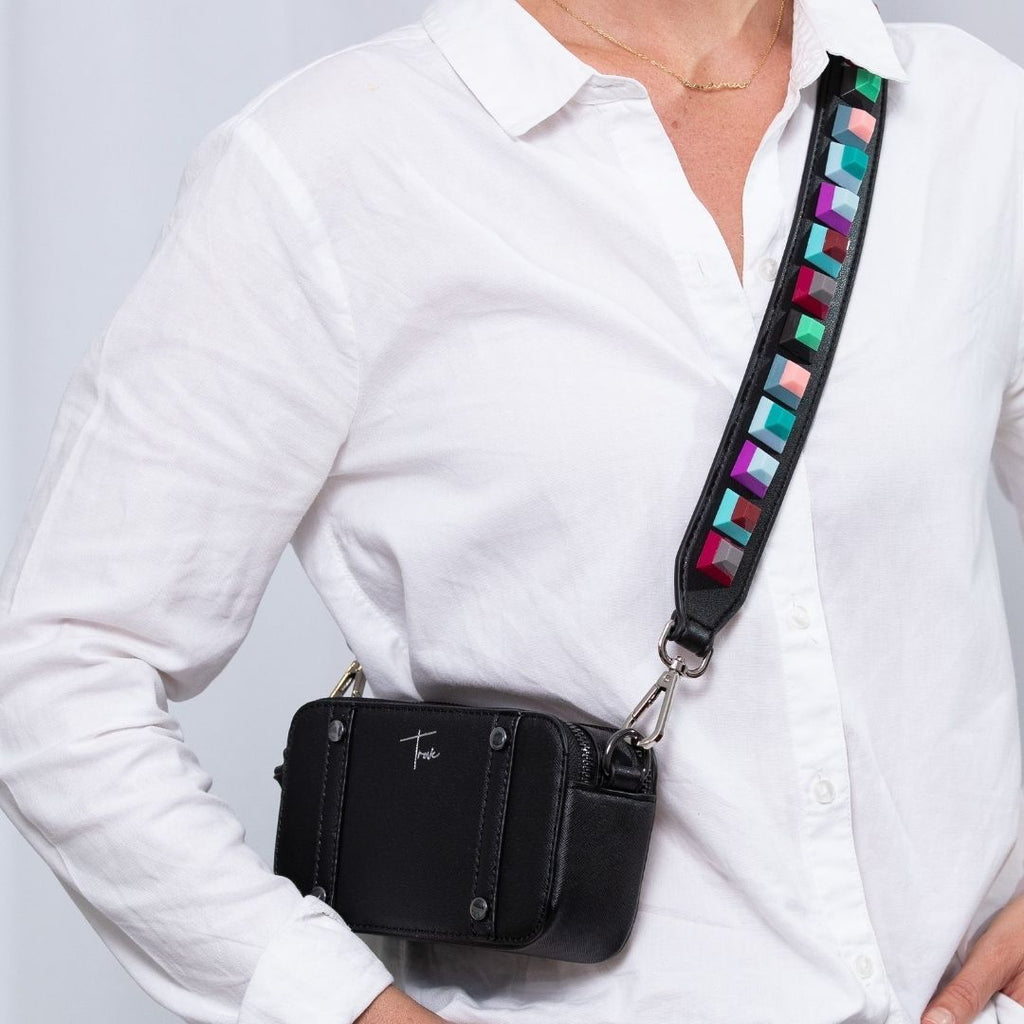 Photo of girl wearing black vegan leather, camera style handbag and black vegan leather bag strap with coloured acrylic embellishments.