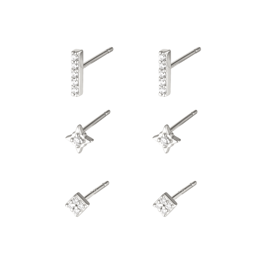 Stock image of silver studs, sold in a three pack, in gold embellished with clear mineral zircon stones. The first earring is a line shape, the second a star shape and the third a square shape.