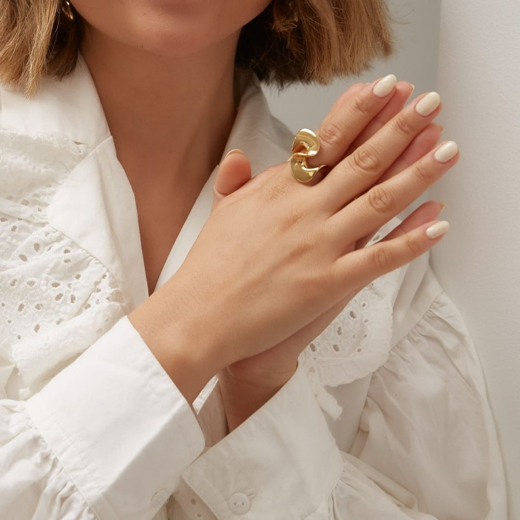Girl wears sterling silver ring in gold that features a large knot shape.