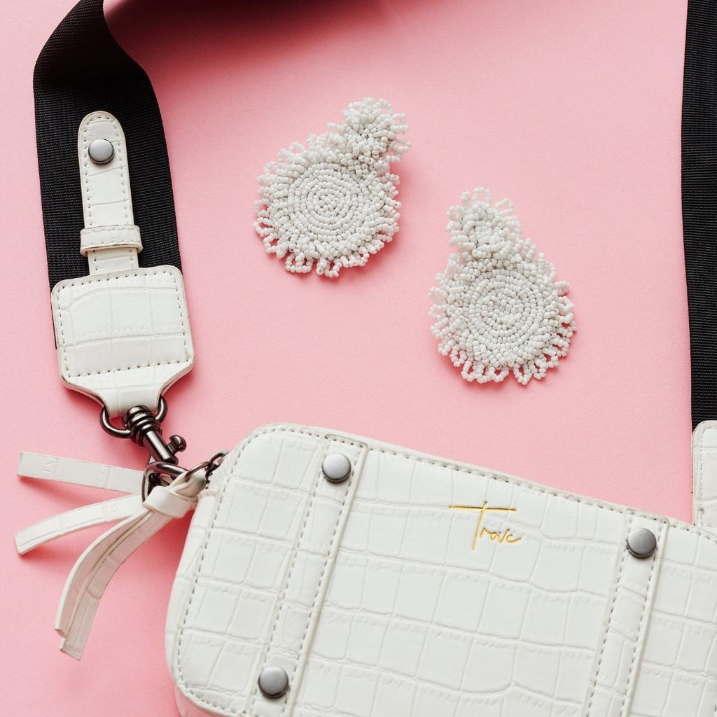 Product photo of oversized, micro bead statement earrings in white. The earrings have a small circle of beads at top and a larger circle of beads attaches to this and forms the drop section of the earring. The earrings sit next to a white, patent, vegan leather cross body camera bag on a pink background.