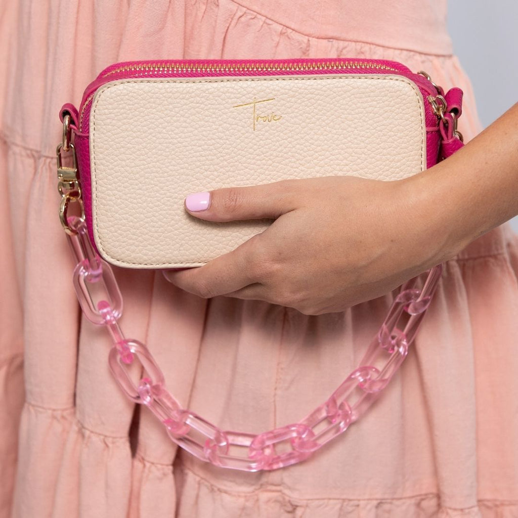Girl holding pink acrylic chain handbag strap attached to small pink camera style handbag.