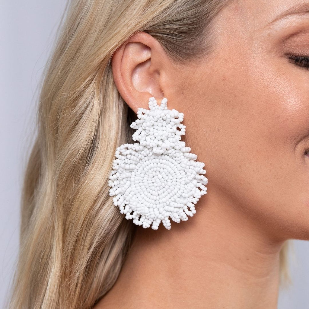 Girl wears oversized, micro bead statement earrings in white. The earrings have a small circle of beads at top and a larger circle of beads attaches to this and forms the drop section of the earring.