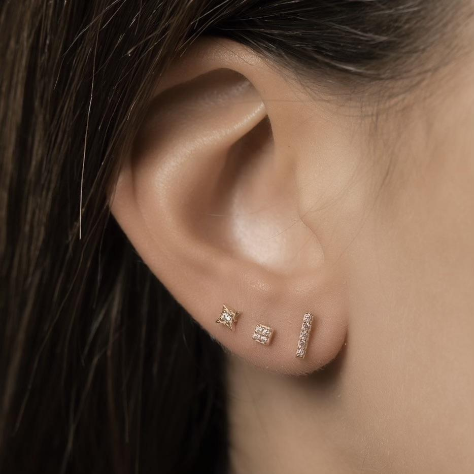 Girl wears gold studs, sold in a three pack, in gold embellished with clear mineral zircon stones. The first earring is a line shape, the second a star shape and the third a square shape.
