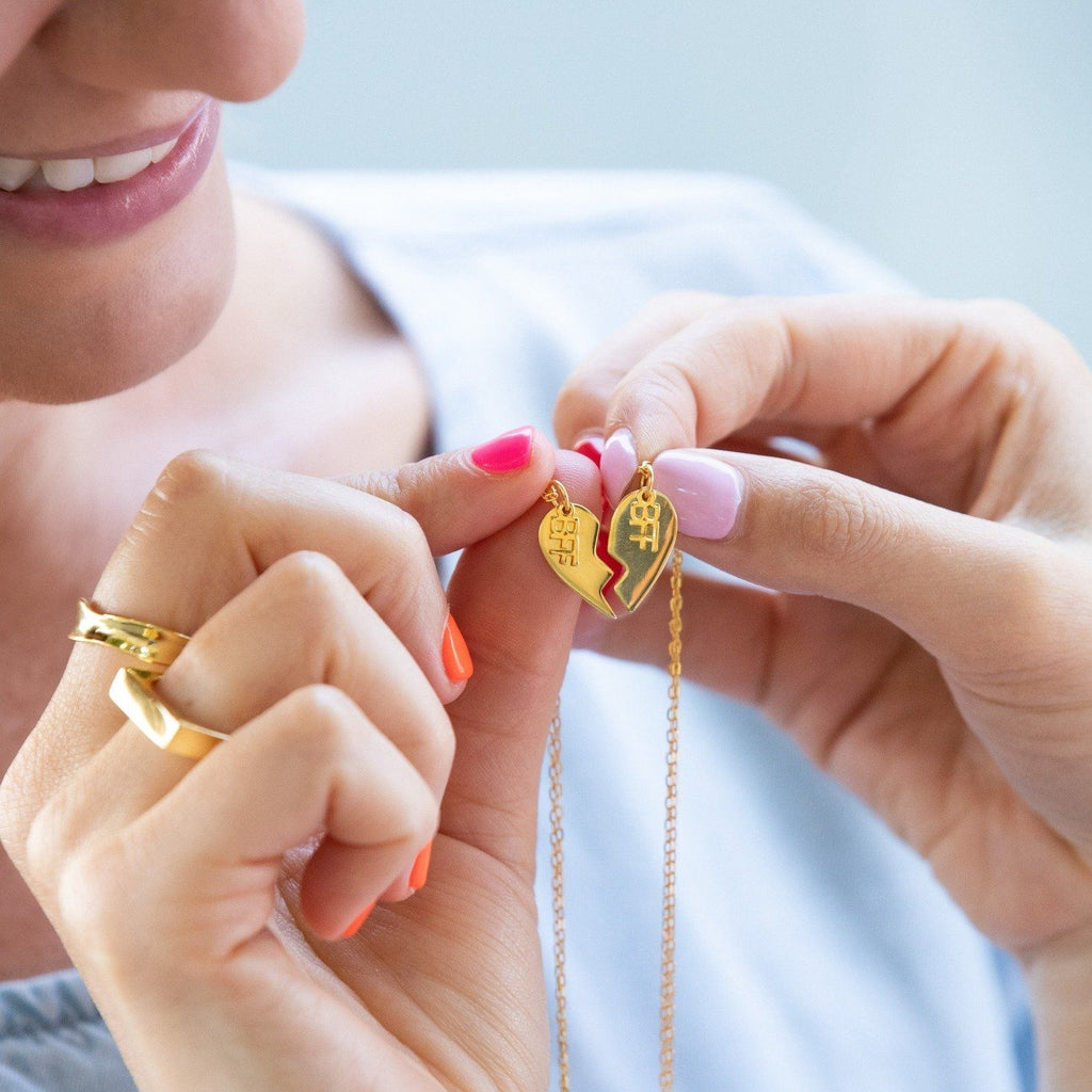 Two women hold a pair of 14k gold plated, sterling silver best friend necklaces, with 14k gold plating, that when put together, make the shape of a heart. Each side of the heart has a charm attached with the word 'BFF