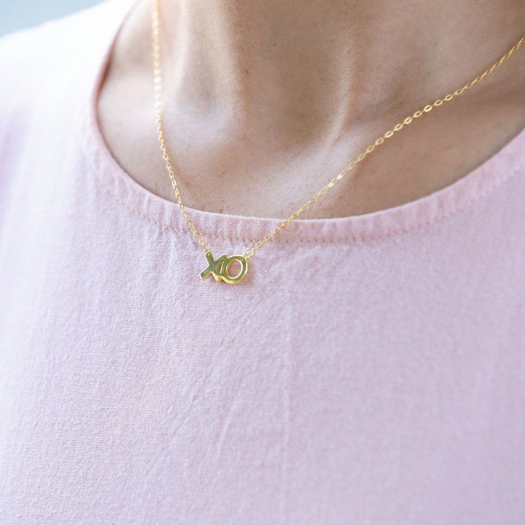 Woman wears a sterling silver necklace with 14k gold plating, that features 'XO' in text .