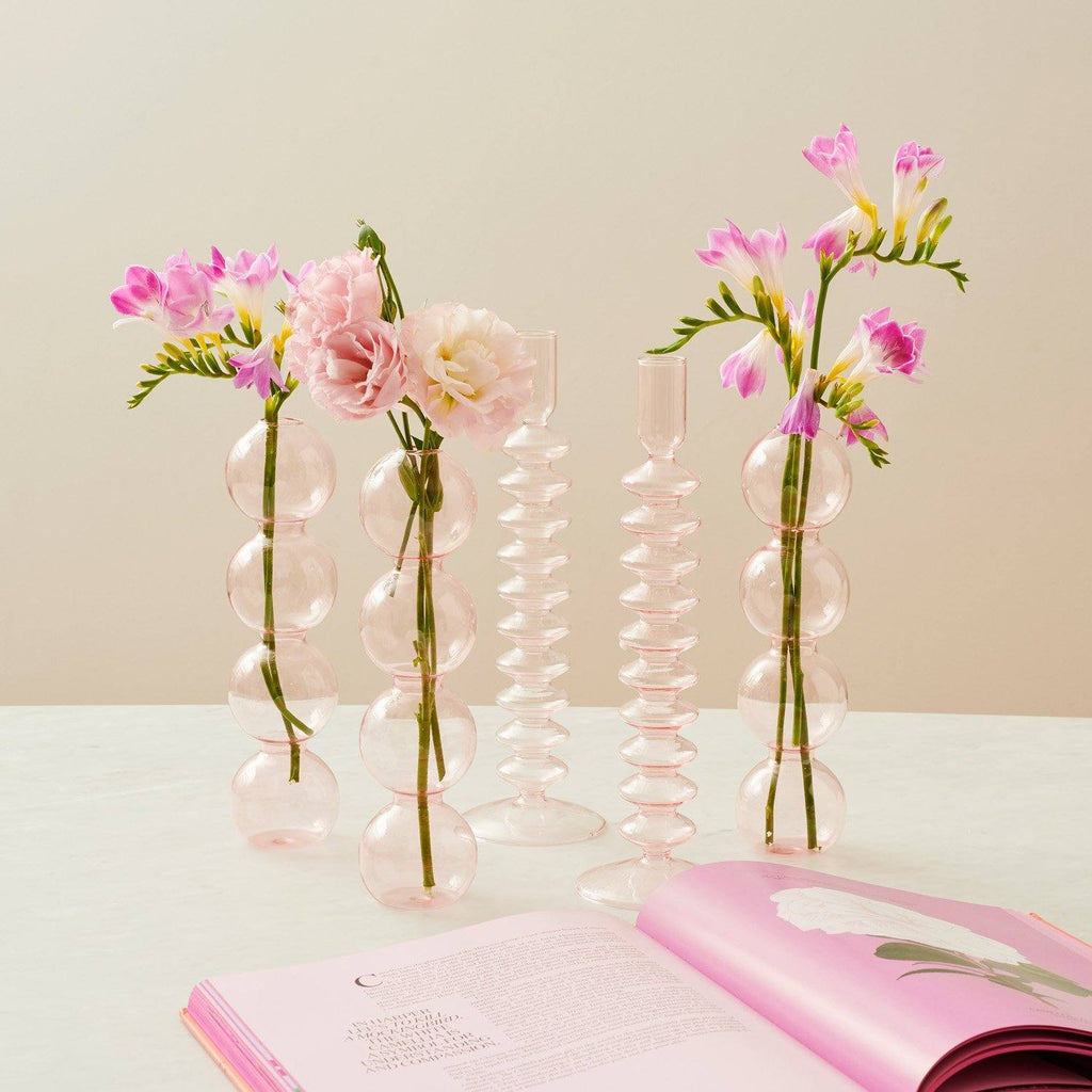 A collection of pink glass vases styled with pink vases on a table next to an open book.
