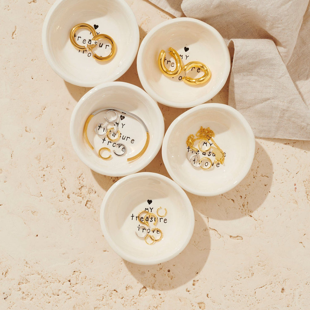 Flat lay image of five small ceramic dishes with jewellery inside