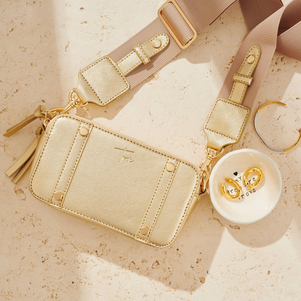 Flatlay image of gold cross body bag sitting next to a white ceramic dish with gold earrings and a gold and silver cuff.