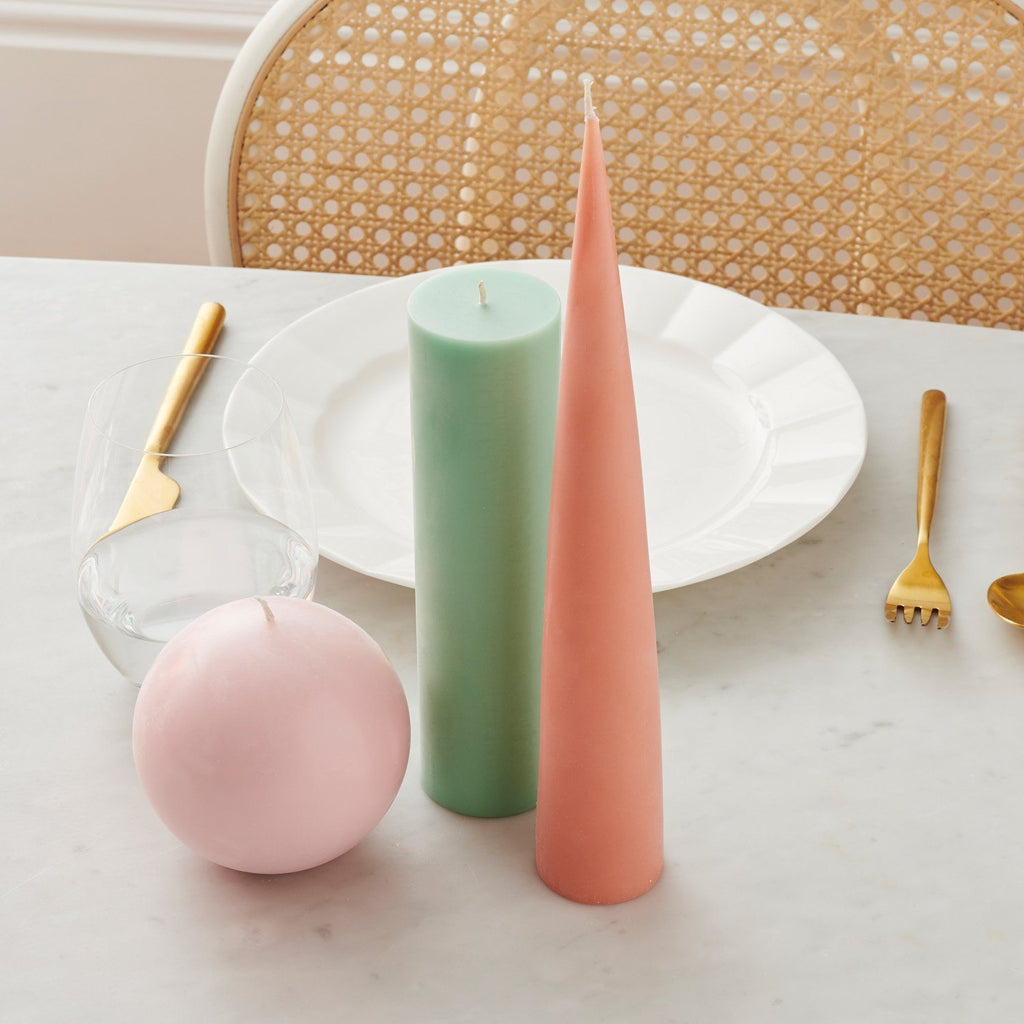 Lifestyle image of a pink spherical candle, mint green pillar candle and peach coloured cone shaped candle next to a table setting.