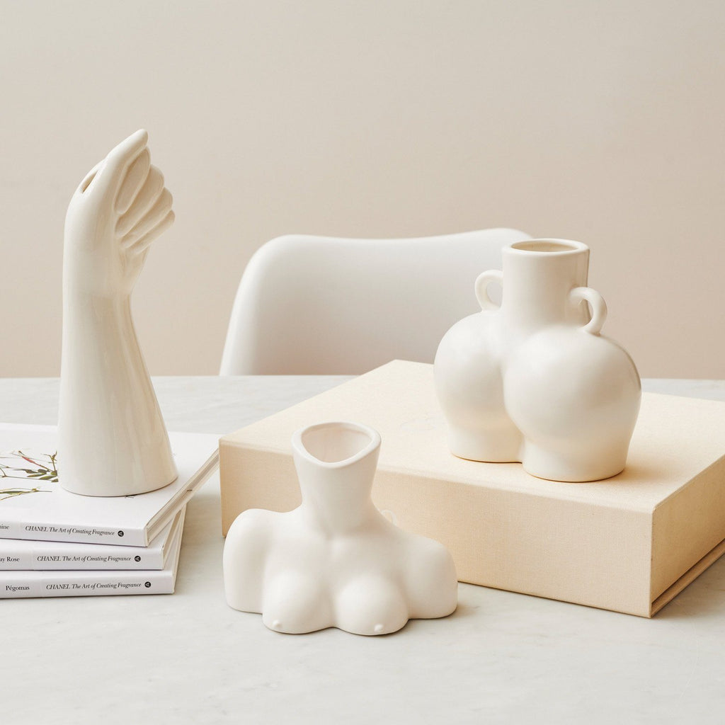 Collection of white ceramic vases in the shape of a bust, a buttocks and a hand.
