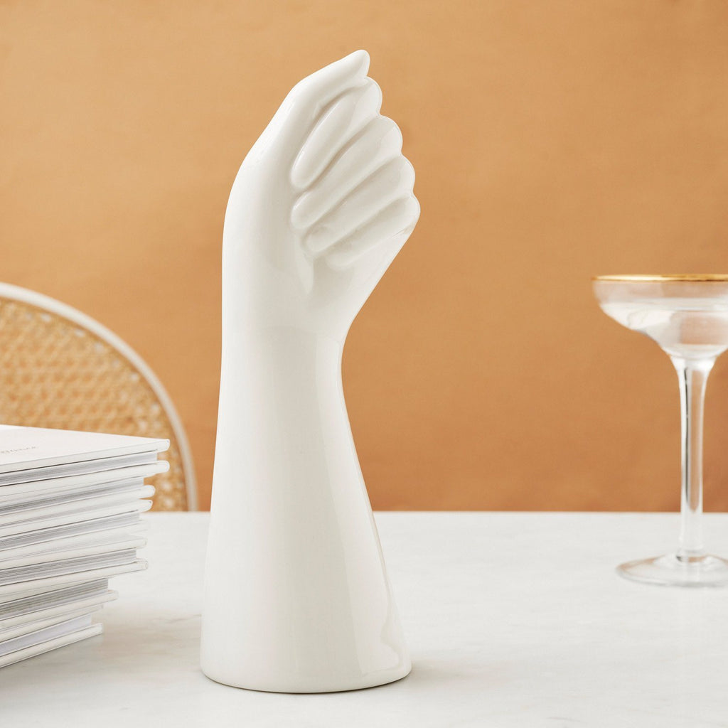Flat lay image of white ceramic vase in the shape of a hand, next to a cocktail glass.