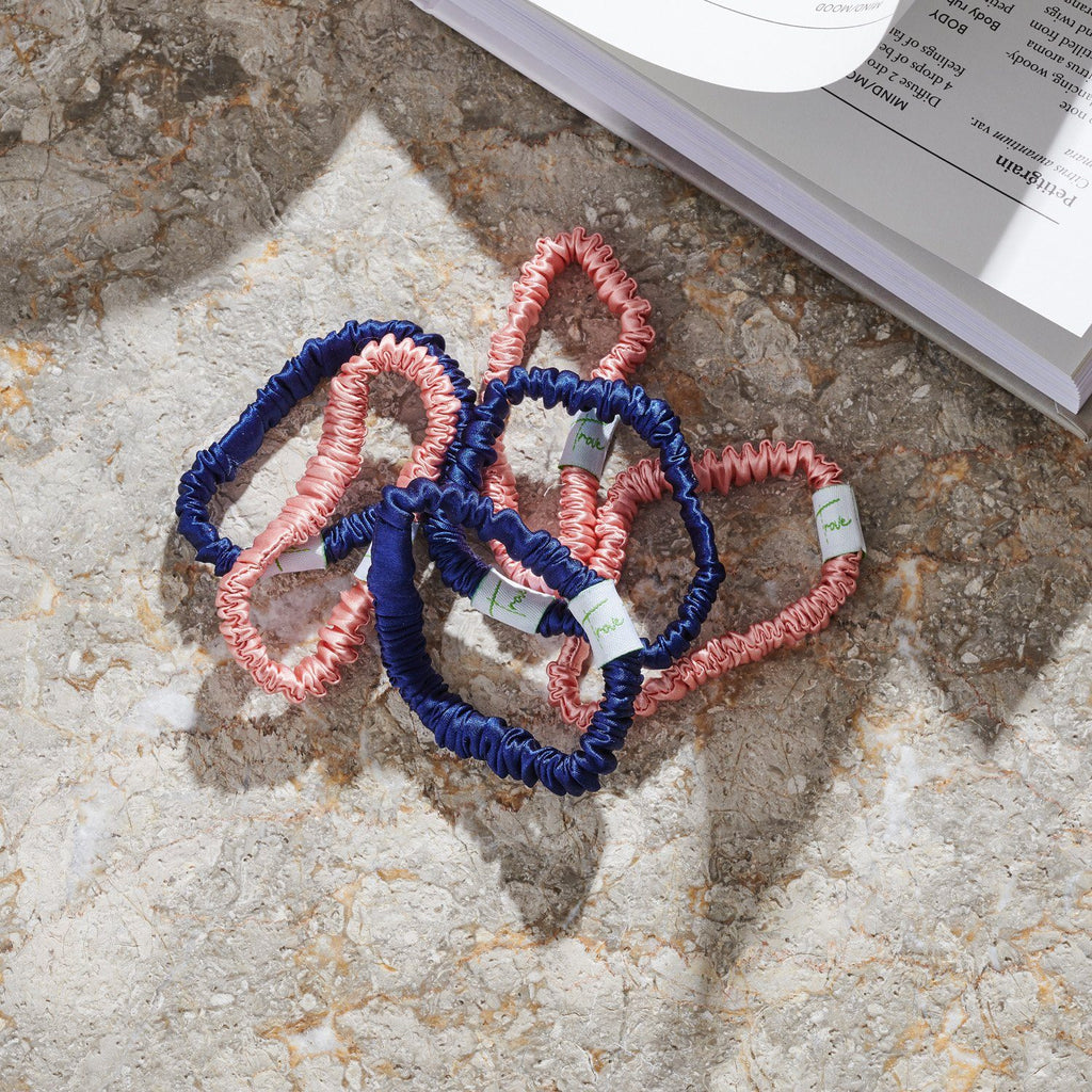 A pile of pink and navy blue scrunchies sit next to a book
