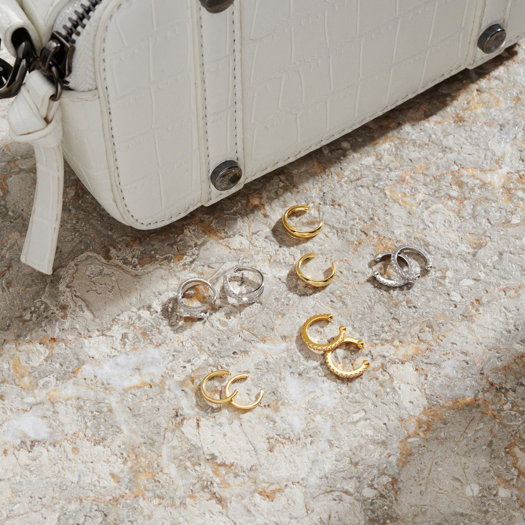 Flat lay image of a collection of ten ear cuffs in gold and silver, sitting next to a white vegan leather handbag.