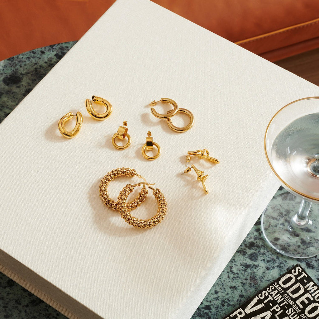 Flat lay image of a collection of gold plated hoop earrings sitting on a closed book next to a cocktail glass.