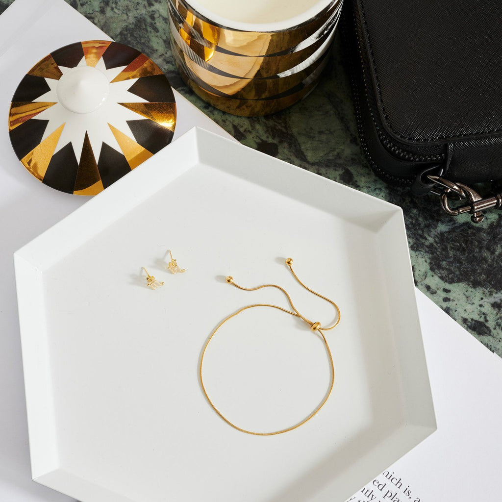 Lifestyle image of gold skinny anklet on a white tray with small gold zodiac studs.