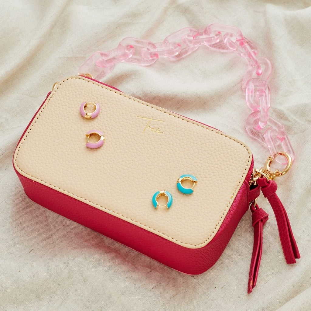 Flatlay photo of pink acrylic chain handbag strap attached to small beige and pink camera style handbag. Styled with pair of blue and pink enamel hoops.