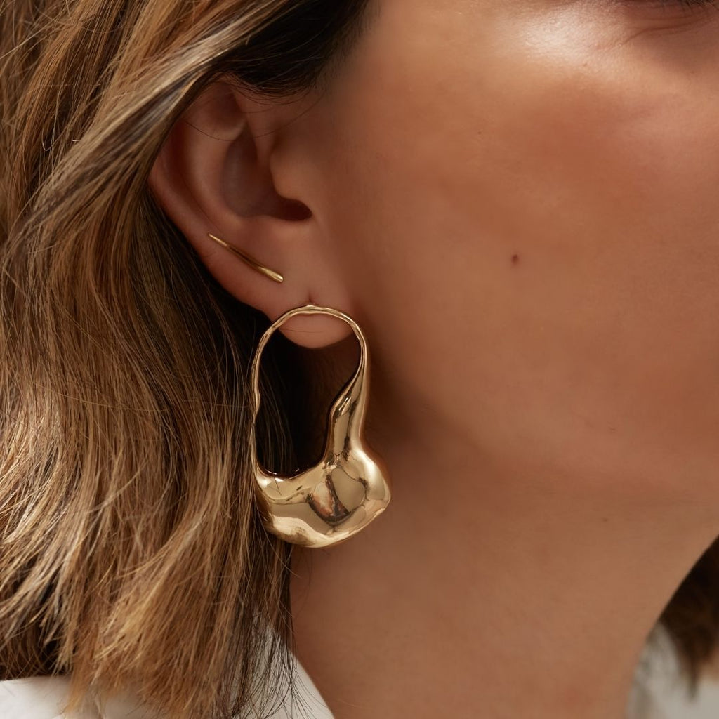 Photo of girl's ear with statement gold earring in first lobe piercing and dainty gold ear climber in second lobe piercing.