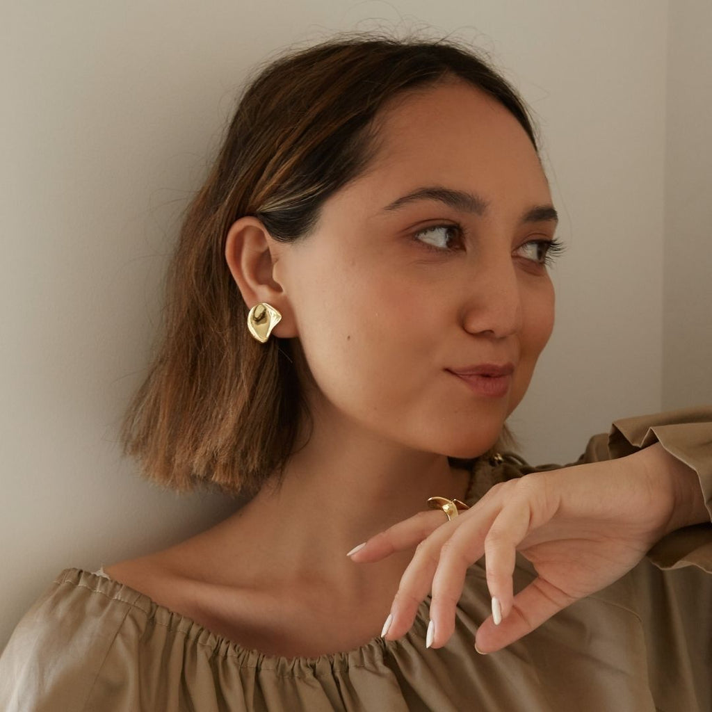 Portrait photo of girl wearing gold plated statement earrings.