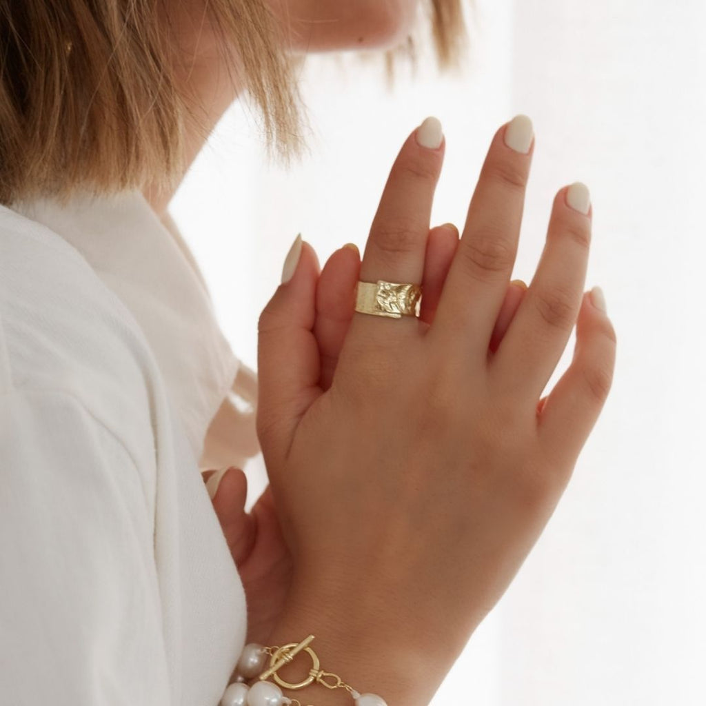 Girl wears gold, adjustable ring with textured finish and freshwater pearl bracelet with gold clasp.